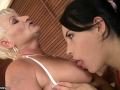 Old and youthful lesbos take a bubble washroom and take up with the tongue some bald pussy